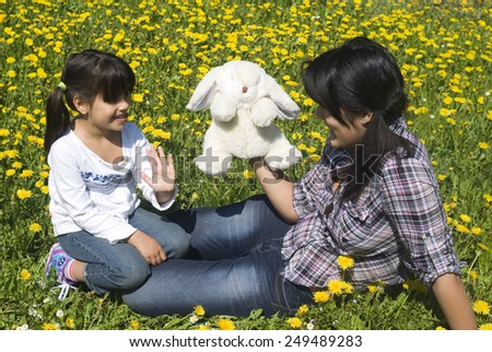 Two sisters playing in spring meadow - stock photo