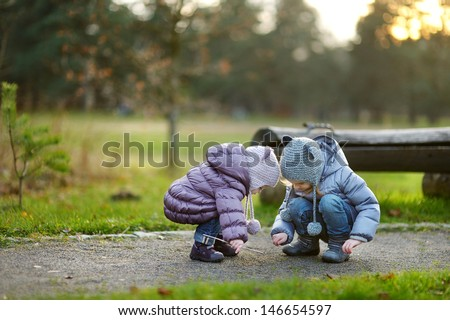 Two sisters playing outdoors on early spring or late autumn - stock photo