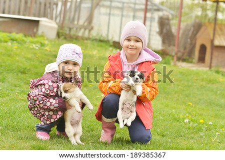 Two sisters playing with puppies  - stock photo