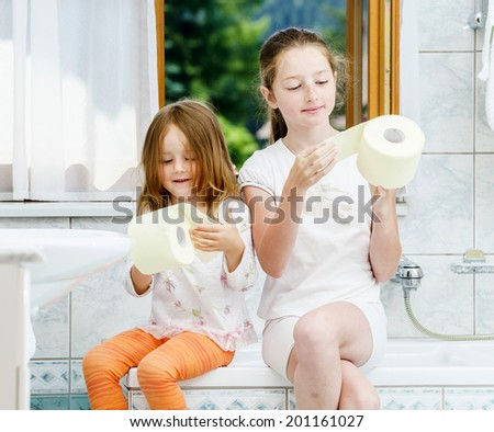 Two sisters playing with toilet paper roll in bathroom - stock photo