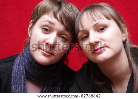 Two sisters pose at the red background - stock photo