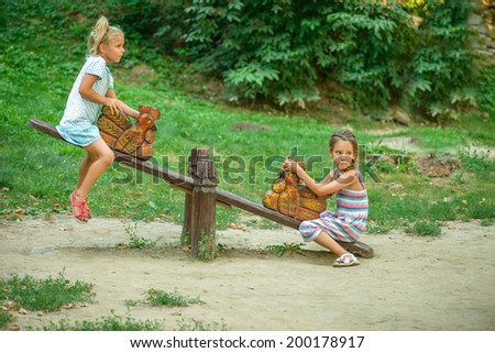 Two sisters ride on swings against summer nature. - stock photo