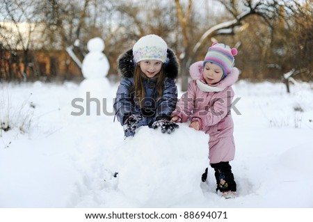 Two sisters rolling snow to make snowman - stock photo