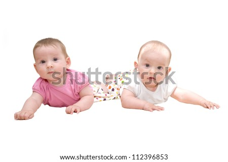 Two sisters, twin baby girls talking and lying together isolated on a white background - stock photo