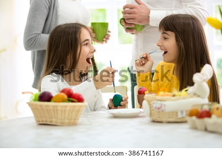 Two sisters twins playful while painted Easter eggs   - stock photo