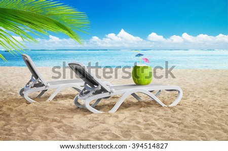 Two sitting place with young coconut on a tropical beach. Green palm leaf, blue ocean and sloudy sky on background - stock photo