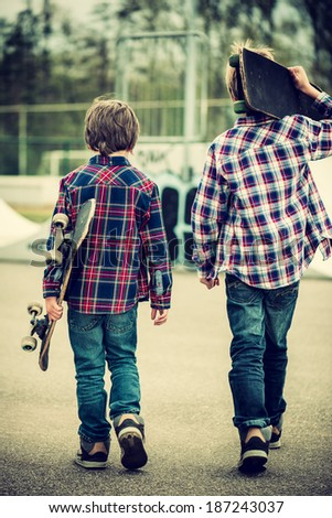 two skater boys walking towards half pipe,vintage effect added - stock photo