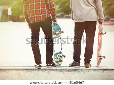 Two skaters posing on a ramp in concrete skate park outdoors. Models holding used old skate boards ready to do tricks.  - stock photo