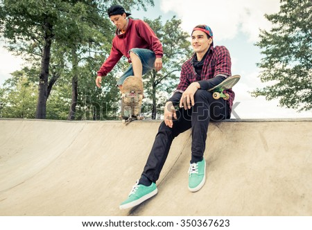 Two skaters practicing at the skate park. Young boys having fun with skateboards - stock photo
