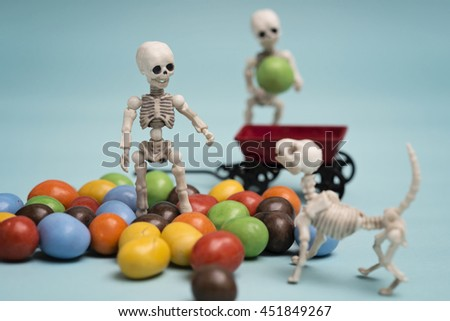 Two skeleton kids with chocolate candy - stock photo