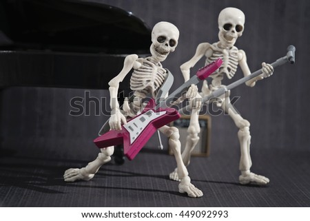 Two skeleton playing rock music - stock photo