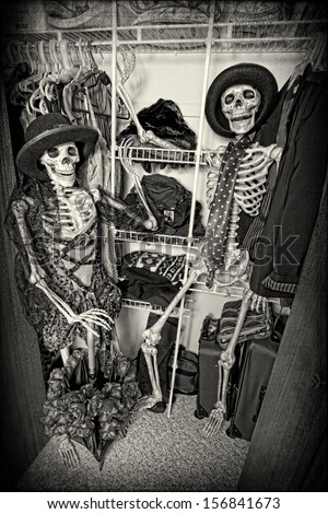 Two skeletons enjoying themselves in someone's closet.  - stock photo