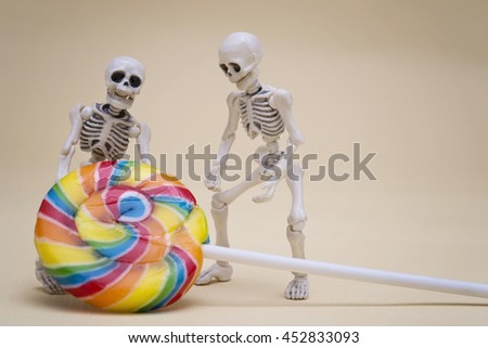 Two skeletons hauling lollipop - stock photo