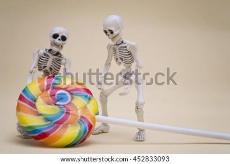 Two skeletons hauling lollipop - stock photo