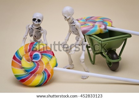 Two skeletons try to move lollipop - stock photo