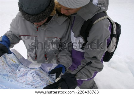Two skier looking into a map - stock photo