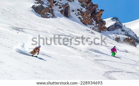 Two Skiers on mountain slope under rocks off piste quickly slide together - stock photo