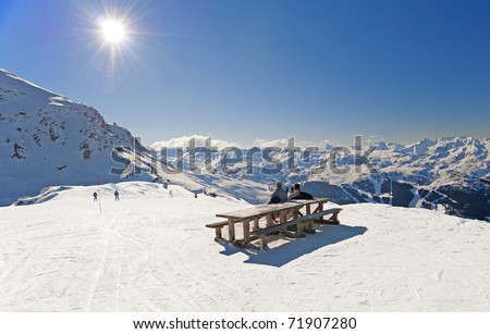 Two skiers sat at picnic table relaxing on piste - stock photo