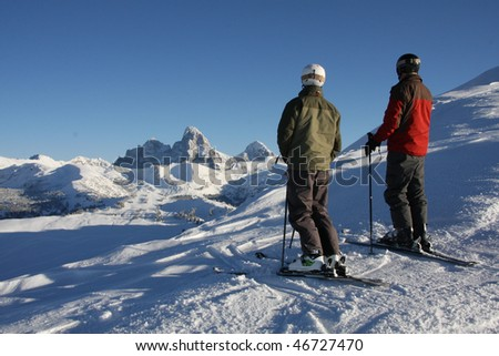 Two skiers view the Tetons - stock photo