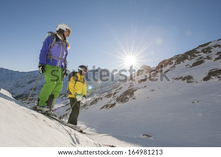 two skiiers watch the departure - stock photo