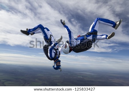 Two skydiver in free-fall in the clouds. - stock photo