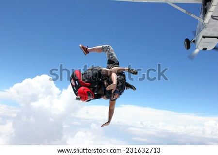 Two skydivers diving out of an airplane - stock photo