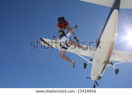Two skydivers exit an airplane - stock photo