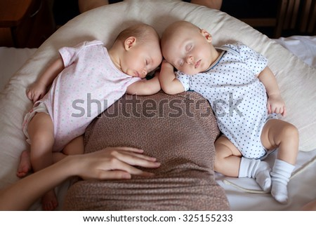 Two sleeping baby and mother at home - stock photo