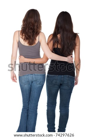 Two slender young women walking away, arm in arm. - stock photo