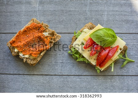 Two slices of artisan grain bread. One with meat spread one with cheese, tomato and basil - stock photo