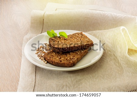 Two slices of brown bread on linen napkin - stock photo
