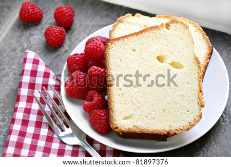 Two slices of fresh pound cake with raspberries on a sunlit windowsill.  Selective focus on upper cake slice. - stock photo