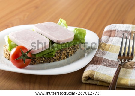 Two slices of ham with bread and cherry tomato on a white plate  - stock photo