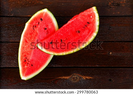 Two slices of watermelon on dark wet wooden table seen from above - stock photo