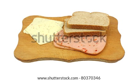 Two slices of wheat bread, pickle and pimento luncheon meat and slices of pepper jack cheese on a wood cutting board. - stock photo