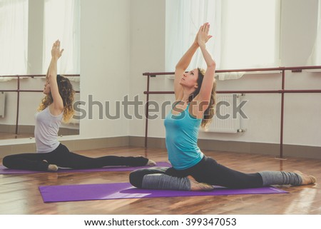 Two slim women are doing stretching for legs - stock photo