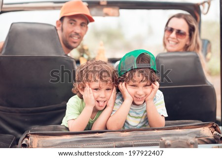 Two small brothers making faces while sitting in the off-road car - stock photo