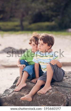 Two small brothers resting on the beach - stock photo
