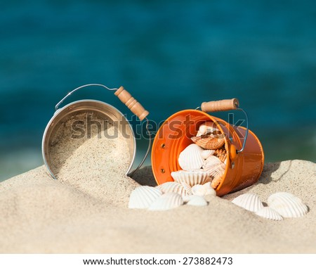 Two small buckets with sea shells on sandy beach with blue background - stock photo