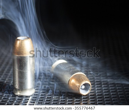Two small cartridges for a handgun with smoke around - stock photo