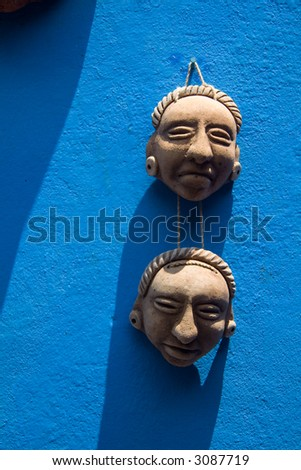 Two small ceramic masks hanging on a bright blue wall - stock photo