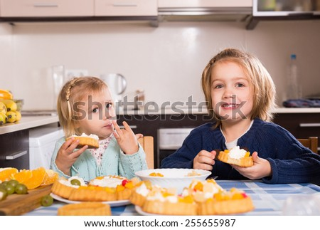 Two small girls eat yummy cream cakes at light kitchen - stock photo
