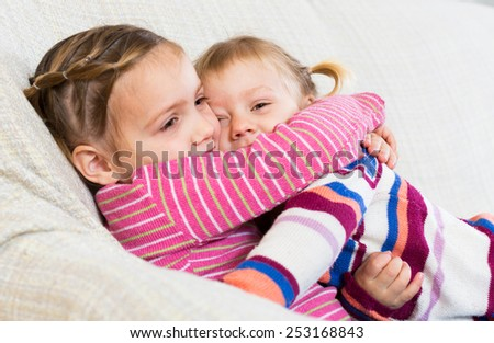 Two small girls embracing and laughing indoors - stock photo