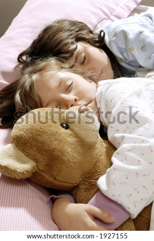 two small girls sleeping and embracing a felt bear - stock photo