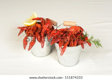 two small pails full of small lobsters with lemon - stock photo