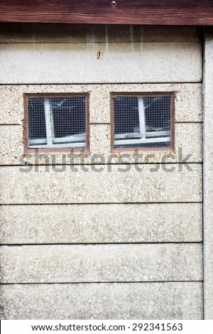 two small square windows in a stone wall - stock photo