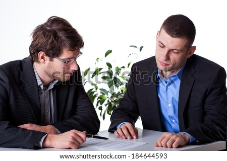 Two smart businessmant analysing a paper agreement at the office - stock photo