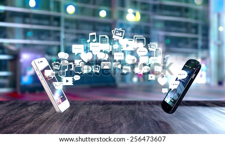 Two smart phones exchanging messages represented as flow of social media related icons. Blurred city background. - stock photo
