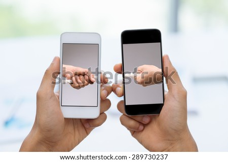 Two smartphones with male hands pulling tug of war - stock photo