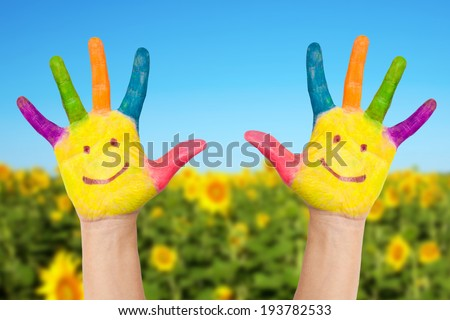 Two smiley hands on a background of field of sunflowers  and blue sky in sunny summer's day. Summer holidays concept. - stock photo
